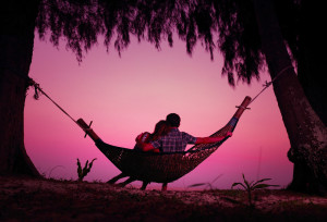 Young couple enjoying tropical sunset in the hammock